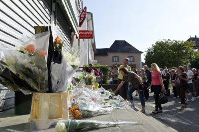 Des fleurs sont déposés devant le tabac où un homme a été tué à Dolomieu le 30 juillet 2014 (Philippe Desmazes / AFP).